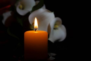 A close up of an orange candle and flame and lily flowers on a dark background.